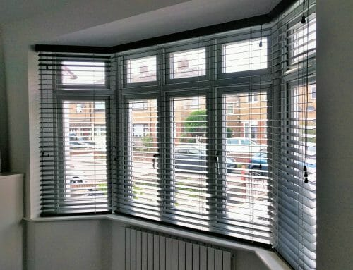 Dark wooden venetians in a splayed bay and showing pelmets